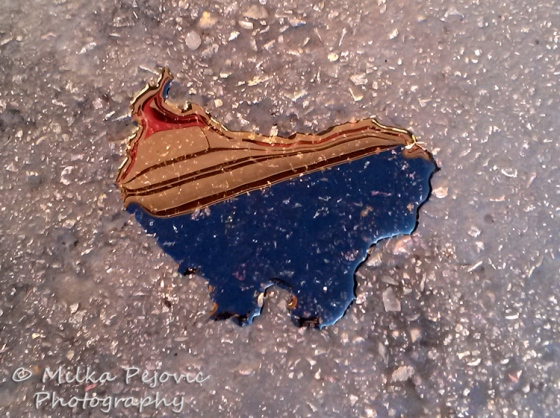 Wordpress weekly photo challenge: Juxtaposition of red, white and blue on a water puddle the shape of the USA